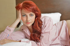 Sexy red haired woman laying in bed Stock Photography