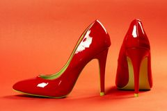 Red high heels shoes. Are on red background royalty free stock images