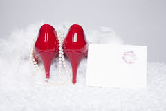 Sexy Red Pumps with Lipstick Kiss. A pair of sexy, red patent leather pumps sit atop a white fur surface with a white background; pearls and a white boa surround Royalty Free Stock Images