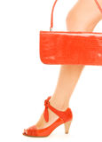 Sexy red shoe. Kit of two classic items, sexy red shoe with high heel on a leg and elegant leather handbag Royalty Free Stock Image