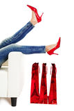 Red Shoes. Female legs with red shoes over christmas presents stock images