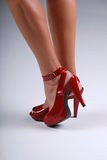 Red shoes. Close up of a womans feet wearing red stiletto shoes royalty free stock images