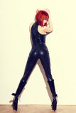 Sexy redhead dominatrix woman in latex catsuit posing at wall. Vintage, bdsm Royalty Free Stock Photography