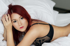 Sexy Redhead girl laying in the white bed Stock Photos