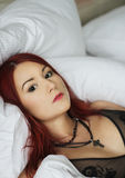Sexy Redhead girl laying in the white bed Royalty Free Stock Images