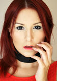 Sexy redhead girl in red dress with black ribbon  Royalty Free Stock Images