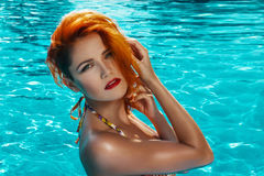 Sexy redhead model posing in pool Stock Images