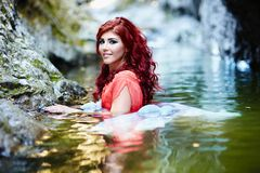 Sexy redhead standing in water Royalty Free Stock Photos