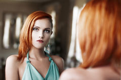 Sexy redhead woman sad in mirror Royalty Free Stock Photography