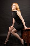 Redhead woman sitting. Over dark background royalty free stock photo