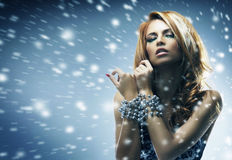 A sexy redhead woman on a snowy background Stock Photo