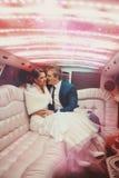 Sexy reizender Mann und Frau merried gerade das Fahren in Limousine Lizenzfreies Stockbild