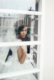 Sexy relaxed brunette bride posing near white window Royalty Free Stock Images