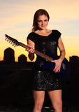 Sexy Rock Star. Attractive woman guitarist in front of city skyline at sunset Stock Image