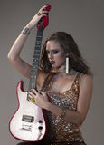 Sexy rocker girl in gold posing with electrical guitar Royalty Free Stock Photos