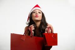 Sexy rode het winkelen van donkerbruine holdingsKerstmis zakken Royalty-vrije Stock Fotografie