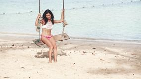 Sexy romantic woman swinging at tropical beach stock footage