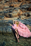 Sexy rosa Ballsaalkleid der schönen blonden Frau, das auf den Felsen in Santorini steht Stockfotografie