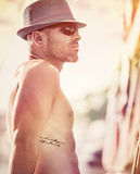 Sailor on sunset. Portrait af a shirtless sailor wearing hat and sunglasses enjoying sunset, man traveling along sea on luxury sailboat, happy summer vacation stock photos