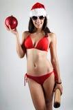 Sexy Sankt-Mädchen im Bikini, der einen Weihnachtsball hält Lizenzfreie Stockfotos