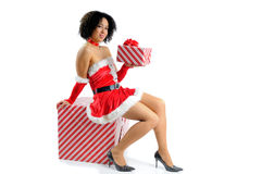 Sexy Santa. Beautiful Mixed Race Young Woman Dressed In A Sexy Santa Costume Sat On A Large Christmas Gift Stock Photos
