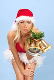 Sexy santa assistant girl with bells. Portrait of sexy young woman wearing santa claus clothes with bells giving a kiss Royalty Free Stock Image