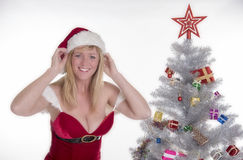 Sexy Santa and Christmas tree. Smiling woman in Santa costume adjusting her hat Royalty Free Stock Images