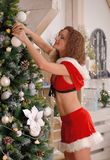 Sexy Santa Claus girl putting Christmas ornaments on the tree Stock Photography