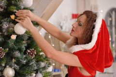 Santa Claus girl putting Christmas ornaments on the tree Stock Photos