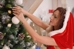 Sexy Santa Claus girl putting Christmas ornaments on the tree Royalty Free Stock Photography