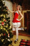 Sexy Santa Claus girl putting Christmas ornaments on the tree Royalty Free Stock Photo