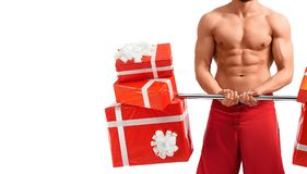 Santa Claus man with a barbell. Presenting Christmas. Horizontal cropped portrait of an astonishing naked Santa with hot fit body working out with a barbell stock image