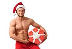 Sexy Santa Claus-Mann mit einem Stapel von Geschenken Stockbild