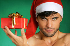 Sexy Santa Claus with present. Sexy Santa Claus holding a Christmas present over green background Royalty Free Stock Photography
