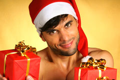Sexy Santa Claus with presents. Sexy smiling Santa Claus holding some Christmas presents over yellow background Royalty Free Stock Photos