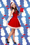 Sexy santa. Collage. Snow maiden in red dress, on dark blue background with stylized artistic snowflakes Stock Photos