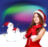 Sexy santa. Collage. Snow maiden in red dress, on dark blue background with stylized artistic snowflakes Royalty Free Stock Photography