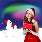 Sexy santa. Collage. Snow maiden in red dress, on dark blue background with stylized artistic snowflakes Royalty Free Stock Photos