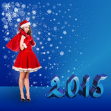 Sexy santa. Collage. Snow maiden in red dress, on dark blue background with stylized artistic snowflakes Stock Photography