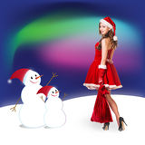 Sexy santa. Collage. Snow maiden in red dress, on dark blue background with stylized artistic snowflakes Royalty Free Stock Images