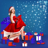 Sexy santa. Collage. Snow maiden in red dress sitting with a lot of present boxes Stock Image
