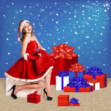 Sexy santa. Collage. Snow maiden in red dress sitting with a lot of present boxes Royalty Free Stock Image