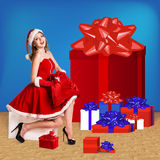 Sexy santa. Collage. Snow maiden in red dress sitting with a lot of present boxes Royalty Free Stock Images