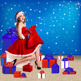 Sexy santa. Collage. Snow maiden in red dress sitting with a lot of present boxes Royalty Free Stock Photos