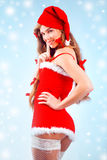 Sexy Santa girl. Sexy mrs. Santa smiling and posing on blue winter backround with snowflakes Royalty Free Stock Photos