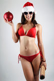 Sexy santa girl in bikini holding a Christmas ball Royalty Free Stock Photos