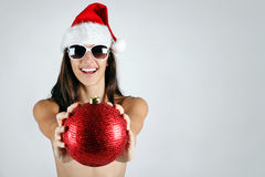 Sexy santa girl in bikini holding a Christmas ball Royalty Free Stock Photos