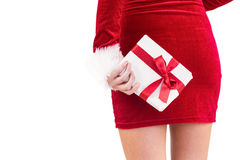 Sexy santa girl holding gift behind back Royalty Free Stock Photography