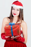 Sexy santa girl holding a gift in her hands and smiling isolated Stock Images