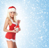 A sexy Santa girl holding a present on a snowy background Stock Photos